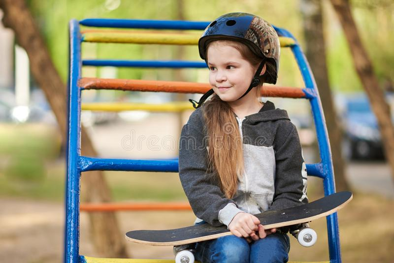 Little girl in a helmet on the playground, with a skateboard in her hands. For any purpose stock photo