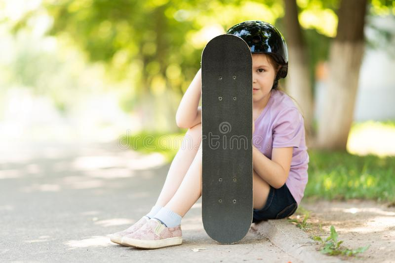 A little girl in a helmet sits and hides behind a skateboard. For any purpose royalty free stock photos