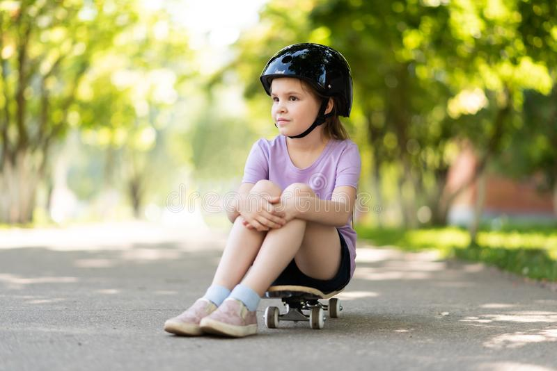 A little girl in a helmet sits on a skateboard and looks into the distance. For any purpose royalty free stock images