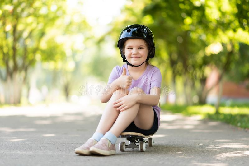 Little girl in a helmet sits on a skateboard and shows a class sign. For any purpose royalty free stock photography