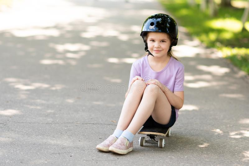 Little girl in a helmet sitting on a skateboard. For any purpose stock image