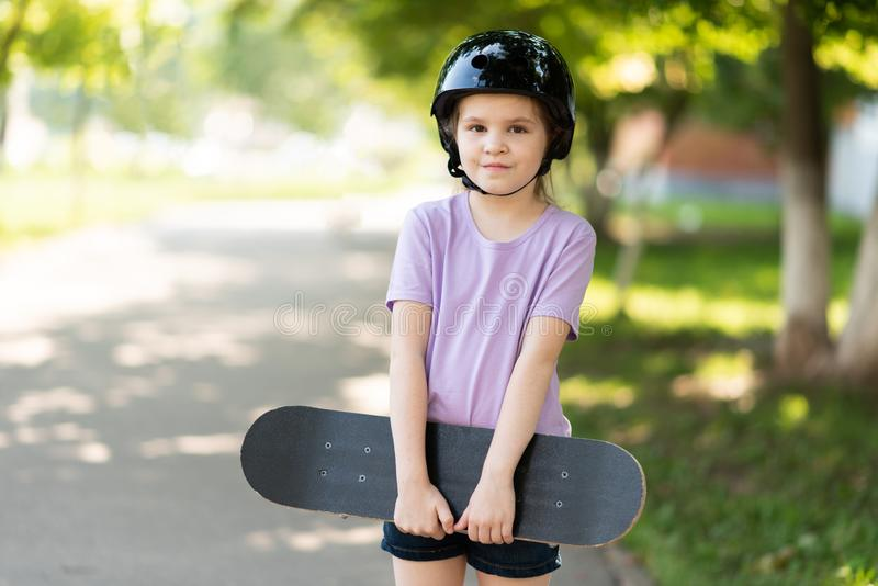 A little girl in a helmet, with a skateboard in her hands, looks into the frame. For any purpose stock image