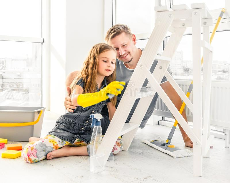Little girl helping dad at cleaning royalty free stock photo