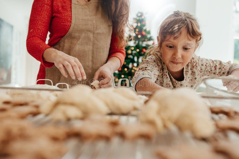 Little girl helping her mother in making cookies for Christmas. royalty free stock images