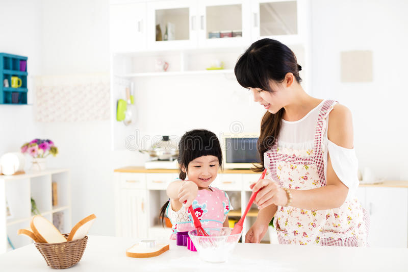 Little girl helping her mother prepare food in the kitchen stock photography