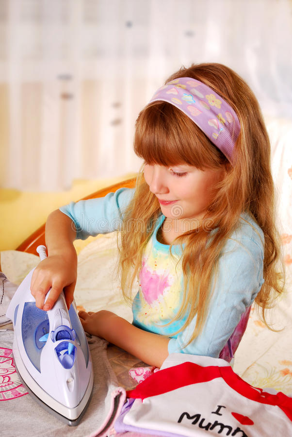 Little girl helping with ironing