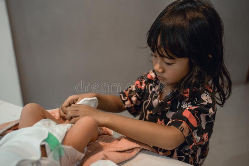 Little girl helping mother change diaper of his newborn baby. At home stock photos
