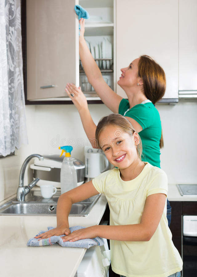 Little girl helping mother at kitchen royalty free stock image