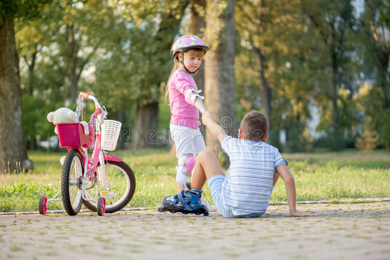 Little girl helps boy with roller skates to stand up. Girl in park, helps boy with roller skates to stand up royalty free stock images