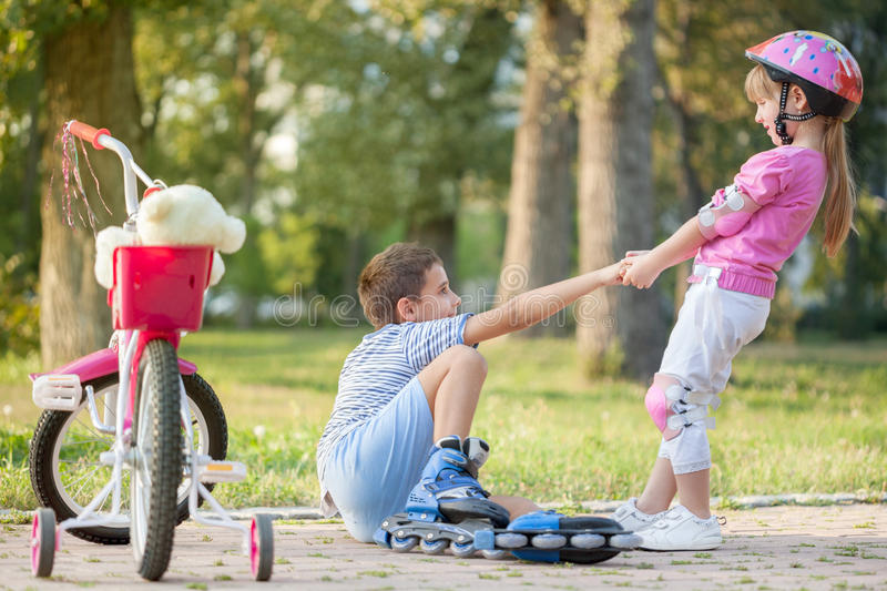 Little girl helps boy with roller skates to stand up. Girl in park, helps boy with roller skates to stand up royalty free stock image