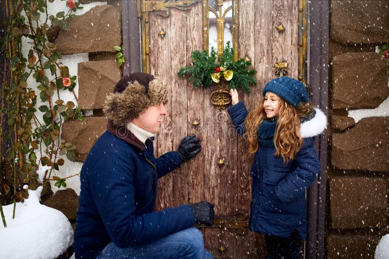 Little girl helps father and hanging Christmas wreath on the door. Cute curly daughter spend time with parents on stock photo