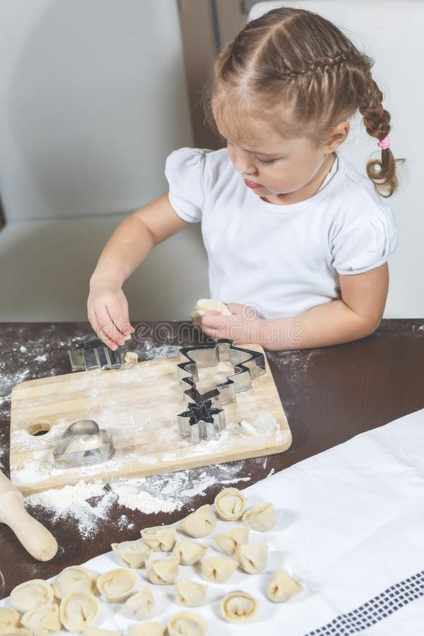 Little girl helps to make dumplings at home royalty free stock images