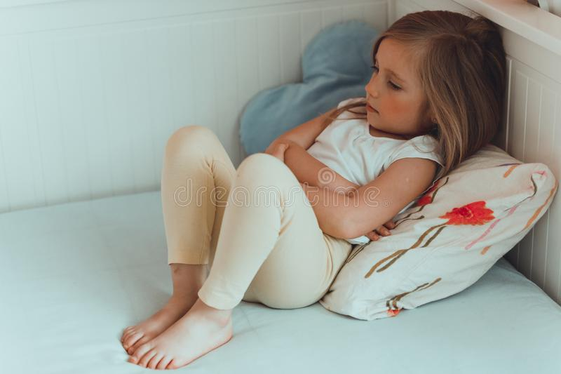 Little girl in her bed has a stomachache. royalty free stock photography