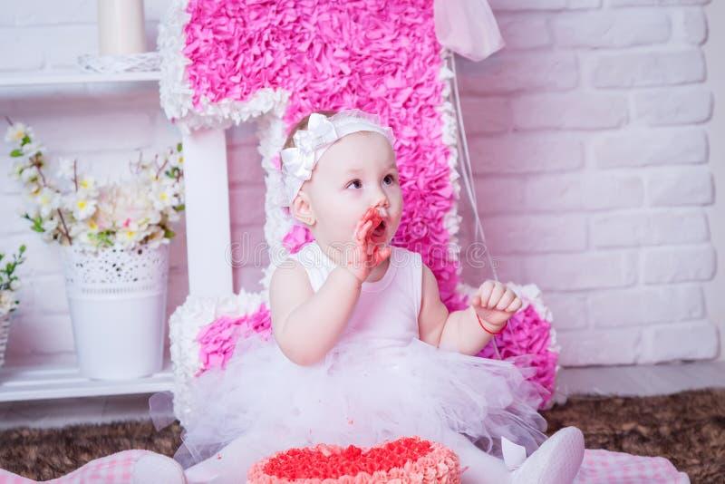 Little girl on her birthday eating cake stock photo