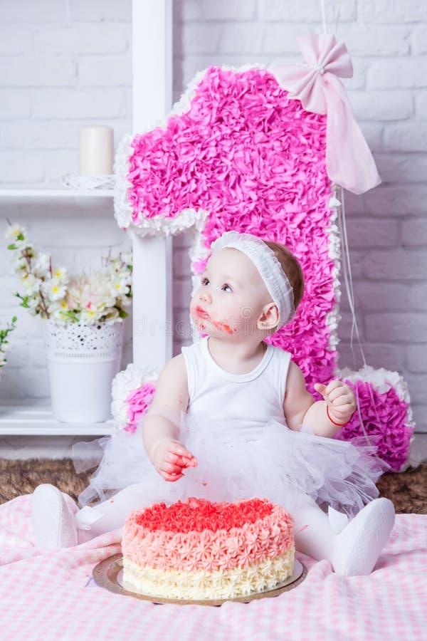Little girl on her birthday eating cake stock photos