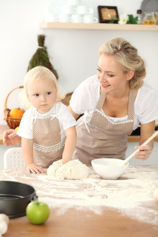 Little girl and her blonde mom in beige aprons playing and laughing while kneading the dough in kitchen. Homemade pastry royalty free stock photography