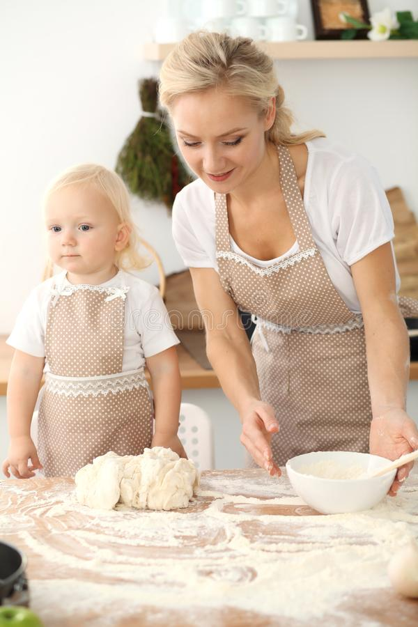 Little girl and her blonde mom in beige aprons playing and laughing while kneading the dough in kitchen. Homemade pastry royalty free stock image