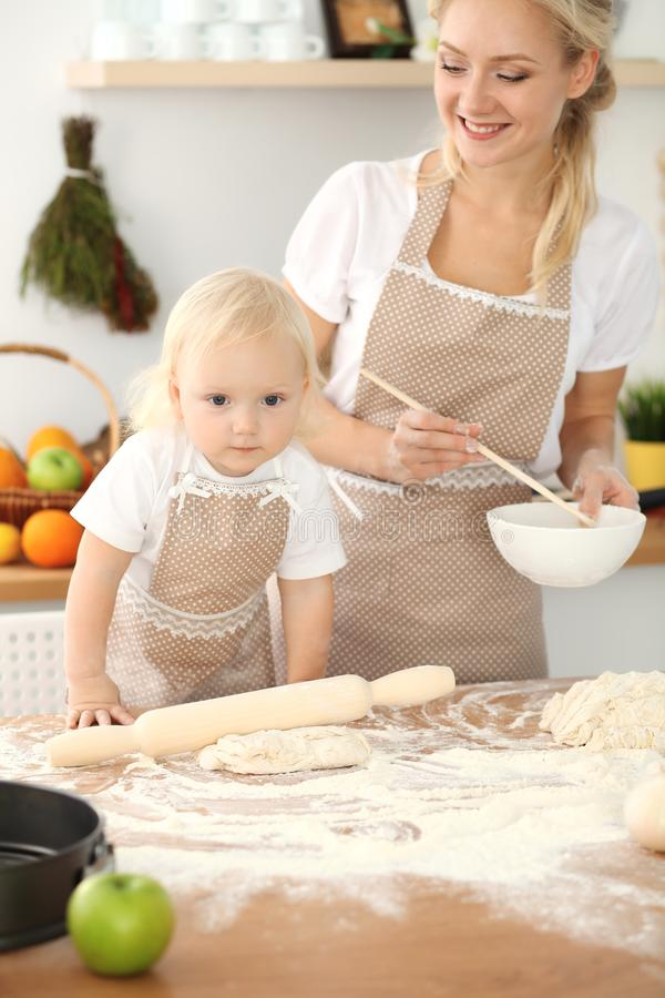 Little girl and her blonde mom in beige aprons playing and laughing while kneading the dough in kitchen. Homemade pastry stock photos