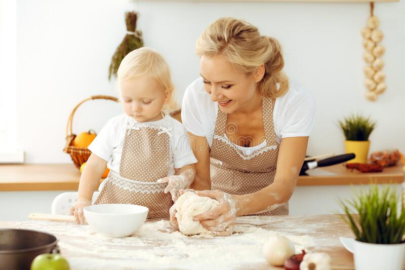 Little girl and her blonde mom in beige aprons playing and laughing while kneading the dough in kitchen. Homemade pastry stock images