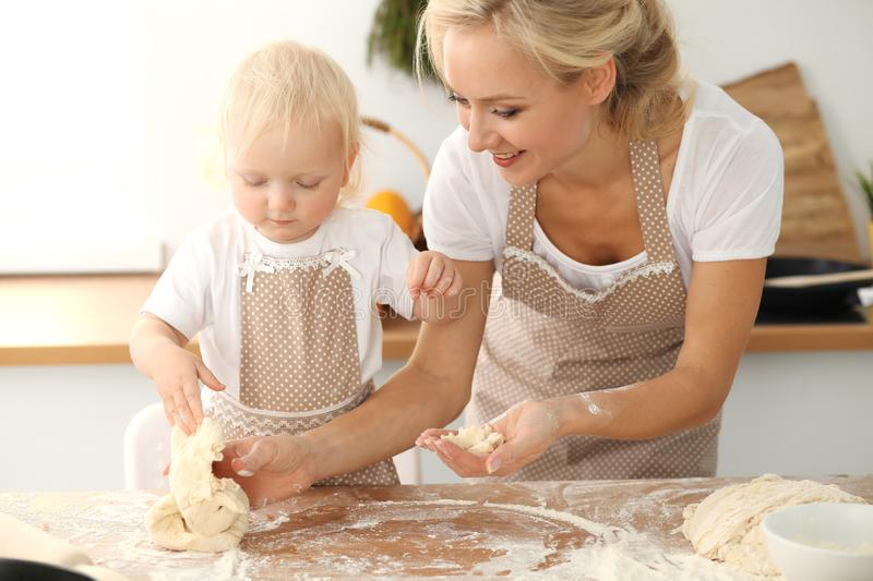 Little girl and her blonde mom in beige aprons playing and laughing while kneading the dough in kitchen. Homemade pastry royalty free stock photo