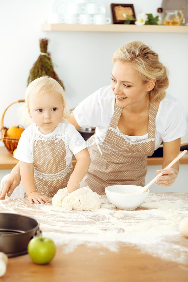 Little girl and her blonde mom in beige aprons playing and laughing while kneading the dough in kitchen. Homemade pastry stock photography