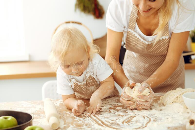 Little girl and her blonde mom in beige aprons playing and laughing while kneading the dough in kitchen. Homemade pastry stock photo