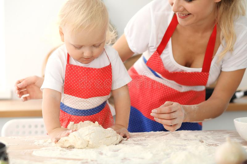 Little girl and her blonde mom in red aprons playing and laughing while kneading the dough in kitchen. Homemade pastry royalty free stock photography