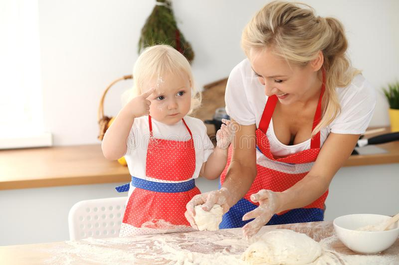 Little girl and her blonde mom in red aprons playing and laughing while kneading the dough in kitchen. Homemade pastry stock photography
