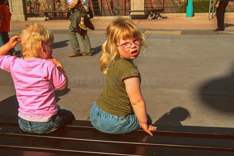 Little girl and her brother sitting on the bench. Travel around Europe. Happy funny families. 05.07.2008, Paris, France. Walking around attractions park. Little royalty free stock photos