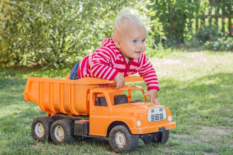 Little girl in her car. A two years old girl playing with her car in the garden stock photography