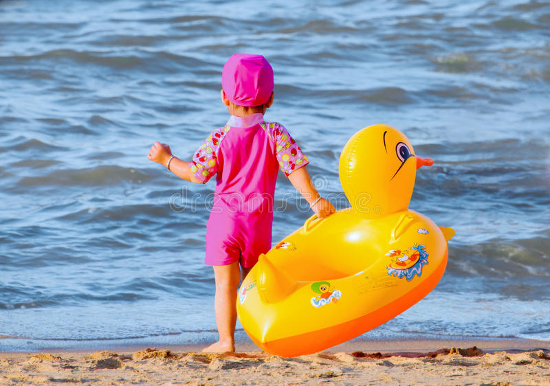 Little girl with her cute swim ring. The little girl is going to swim in sea with her cute swim ring royalty free stock photo