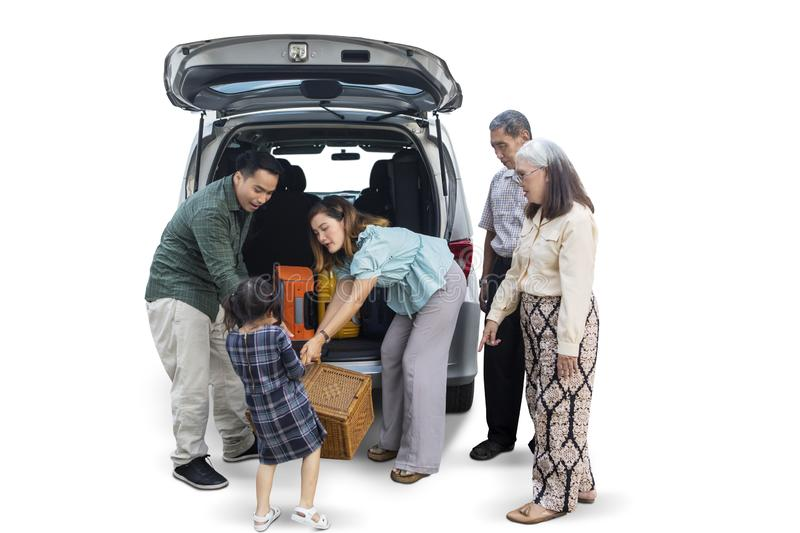 Little girl with her family preparing for vacation. Little girl helping her family to carrying a suitcase into car while preparing for vacation, isolated on royalty free stock images