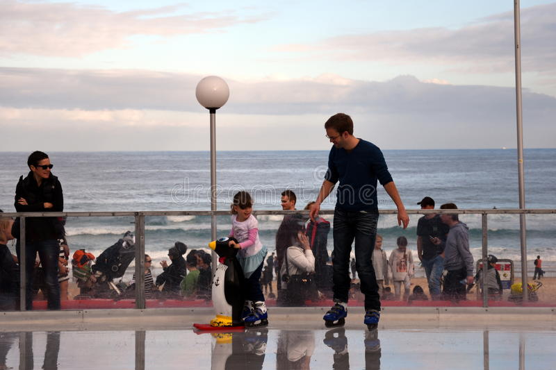 A little girl and her father are ice skating on Bondi ice rink. Sydney, Australia - Jul 17, 2016. A little girl and her father are ice skating on Bondi ice rink stock photos
