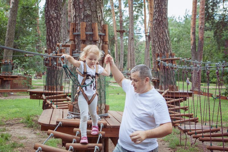 Little girl with her father overcomes an obstacle. royalty free stock photos