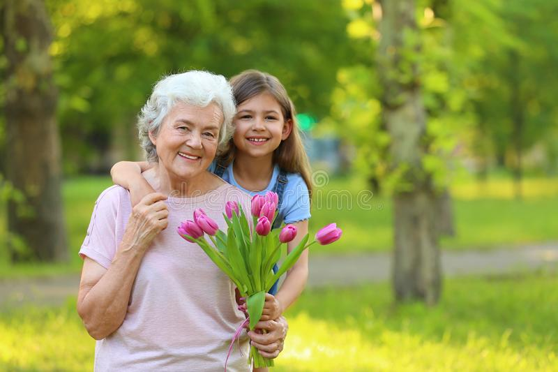 Little girl with her grandmother and  of flowers in park. Space for text stock photos