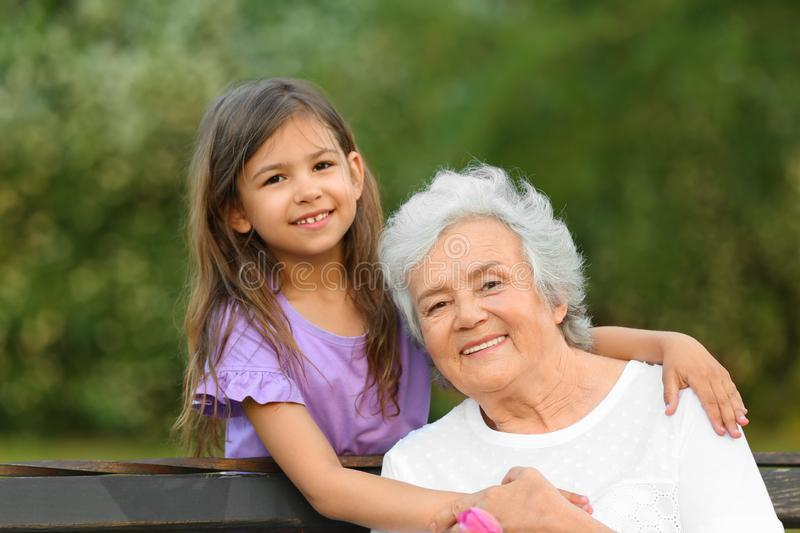 Little girl and her grandmother hugging on bench royalty free stock images