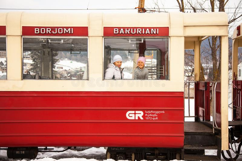 Little girl and her grandmother travelling by Kukushka train in Georgia between Borjomi and Bakuriani villages stock photography