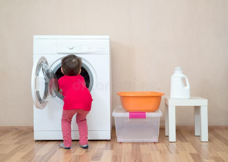Little girl with her hands inside a washing machine stock image