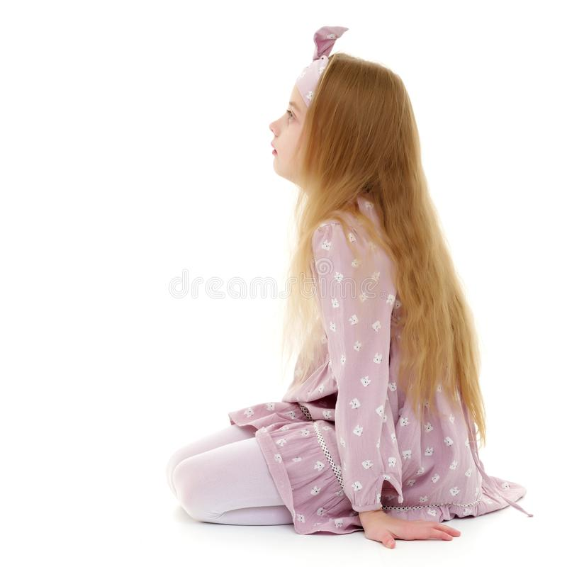 The little girl is on her knees. stock image