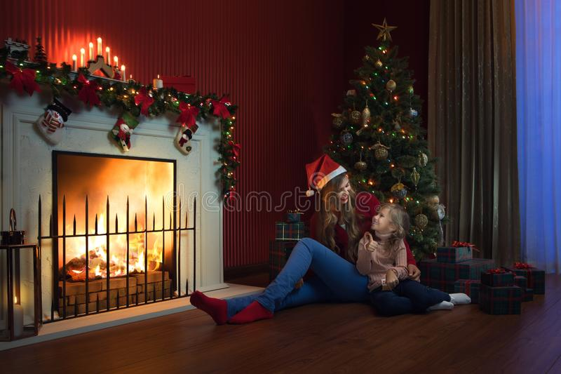 Little girl with her mama in christmas environment stock photo