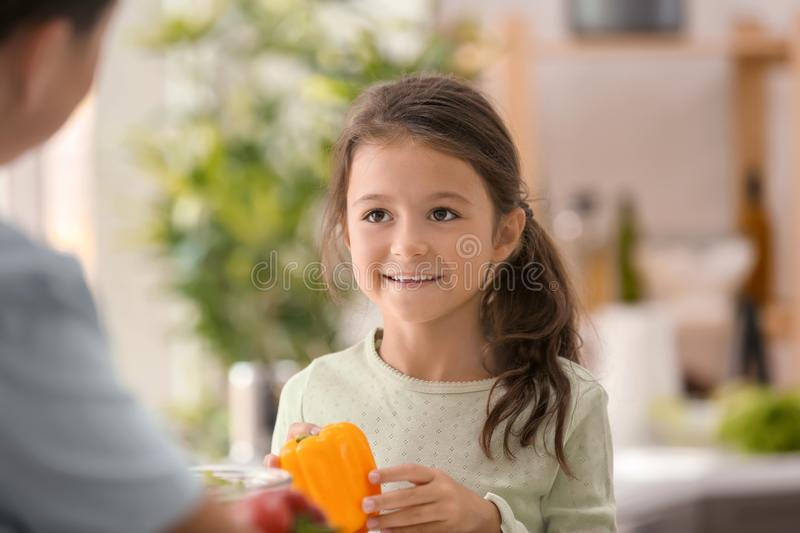 Little girl with her mother cooking together in kitchen royalty free stock photos