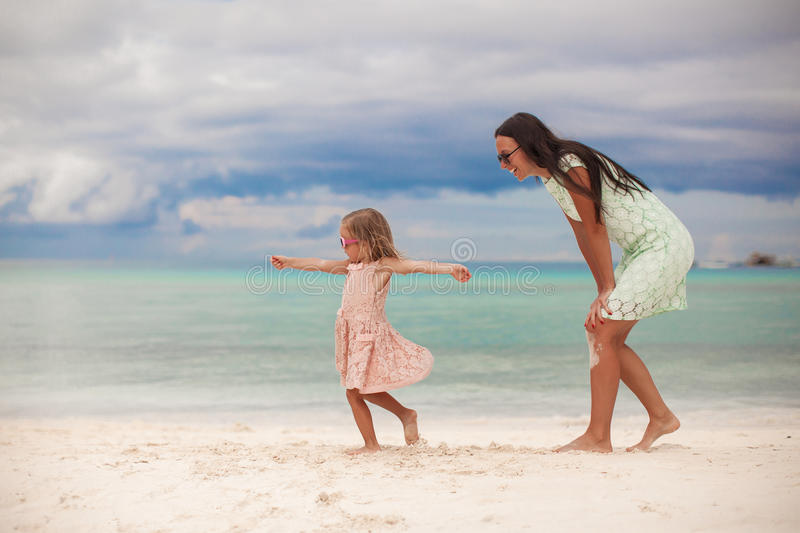 Little girl with her mother dancing at white sandy stock photo