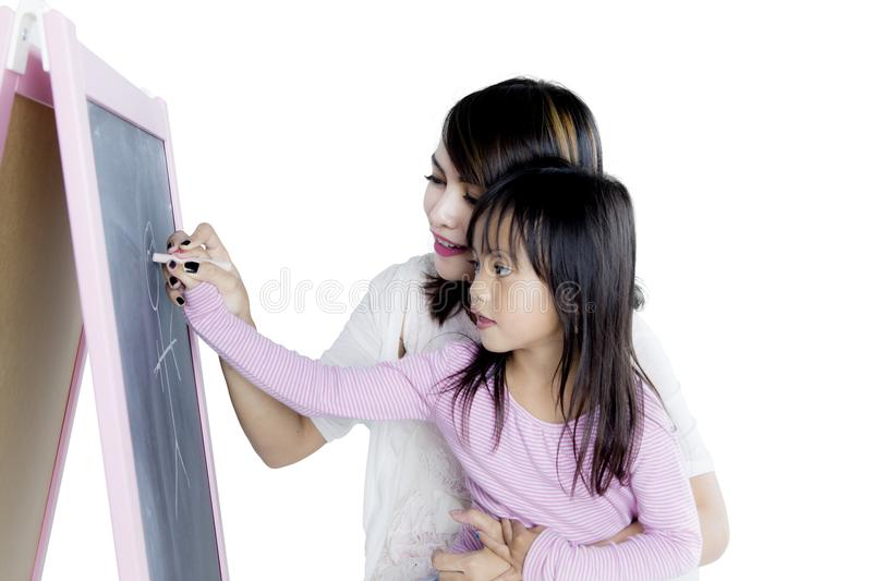 Little girl with her mother drawing with chalk stock photo