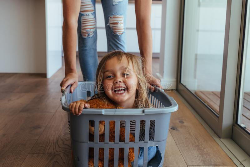 Little girl and her mother having fun doing laundry stock images