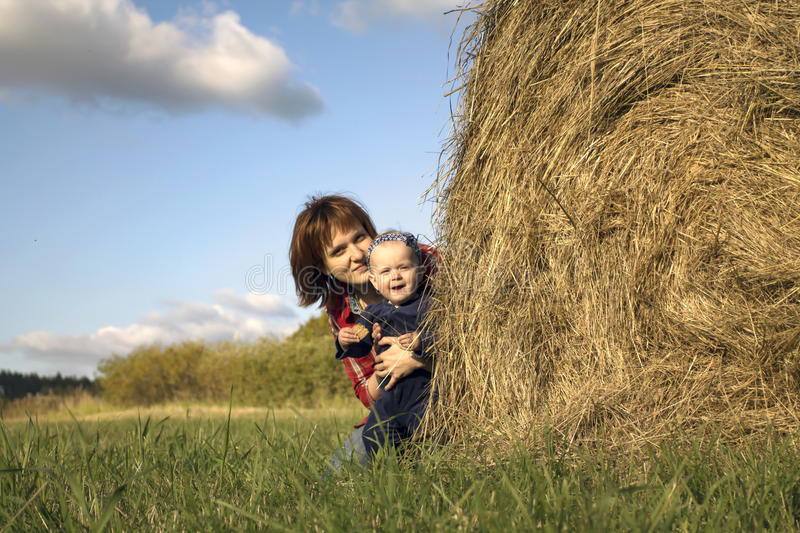Little Girl and Her Mother by the Haystack royalty free stock photography
