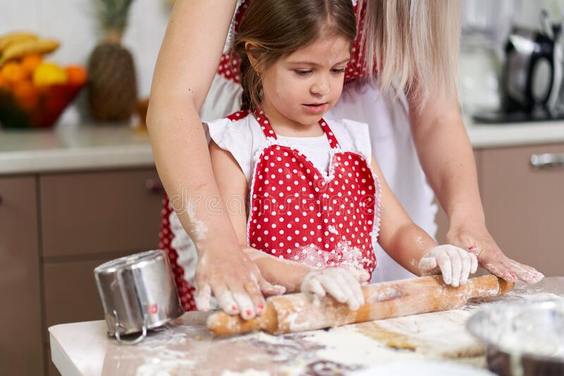 Girl and her mother kneading stock photo