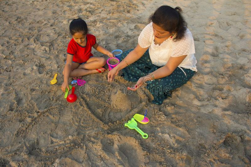 Little girl and her mother making a fort with sand on the beach, Alibag, Konkan, India. royalty free stock photos