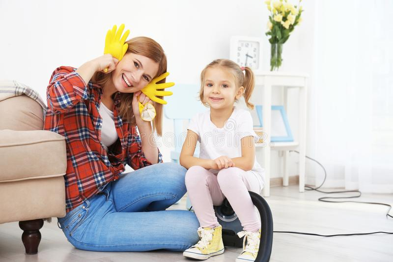 Little girl and her mother playing while doing cleanup stock images