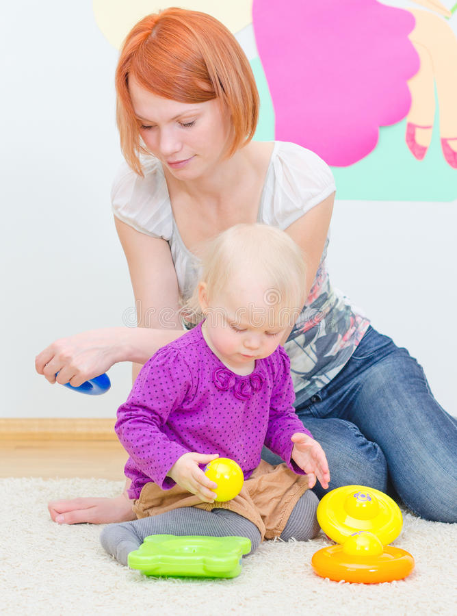 Little girl and her mother playing. stock images