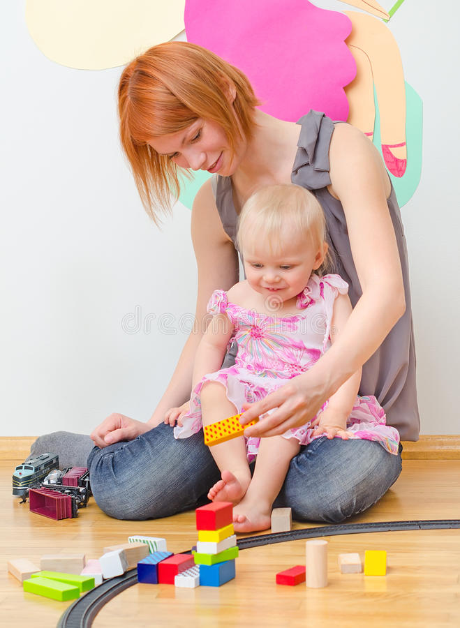 Little girl and her mother playing with railway. stock image